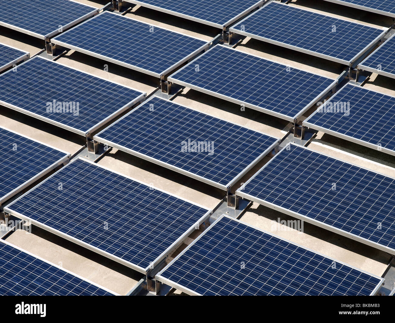 Photovoltaic solar panels on a concrete rooftop. - Stock Image