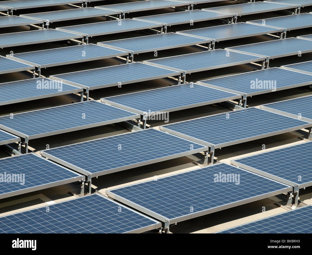 Shiny, new solar panels on a concrete rooftop. - Stock Image