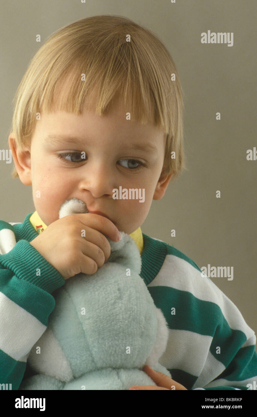 moody looking boy chewing soft toy's ear - Stock Image
