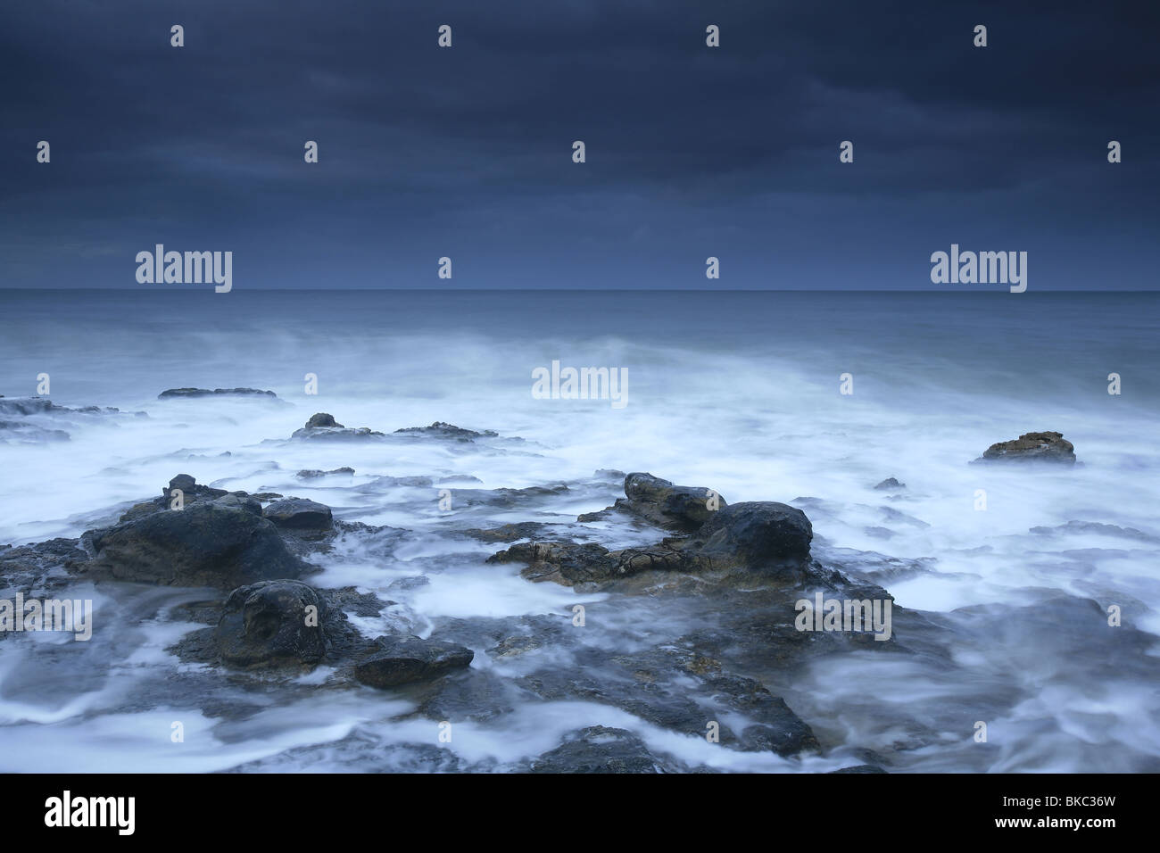 Sea surf and dark clouds at West side cliffs at Santa Cruz, California, USA. - Stock Image