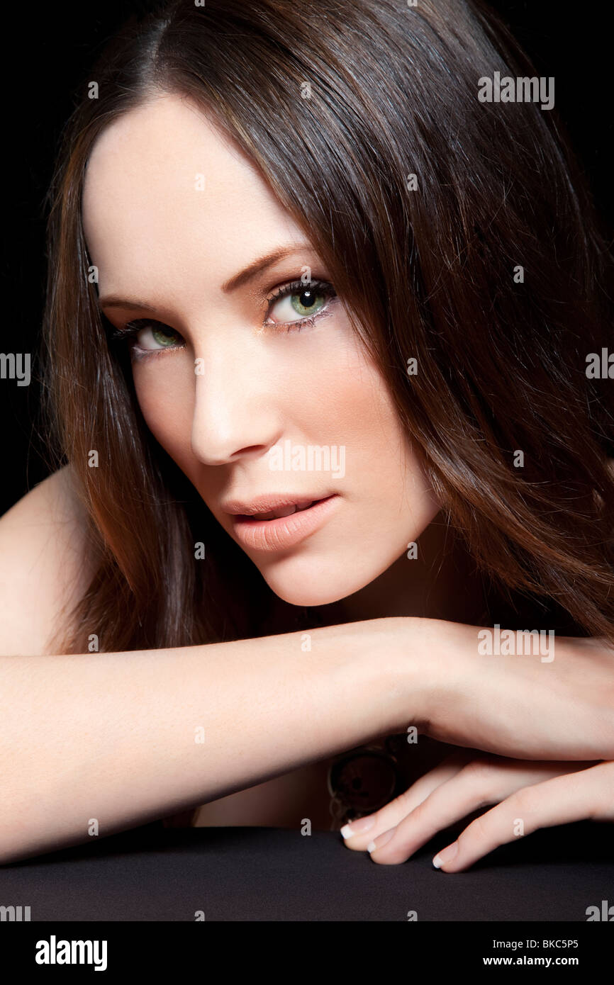 young brunette woman with green eyes beauty shot studio - Stock Image
