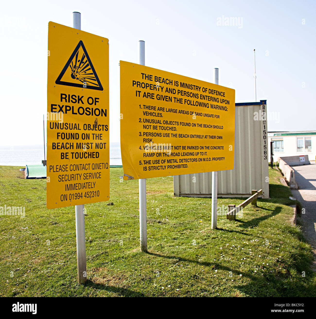 Warning signs for explosives found on beach at Pendine sands with metal detector use prohibited Wales UK - Stock Image