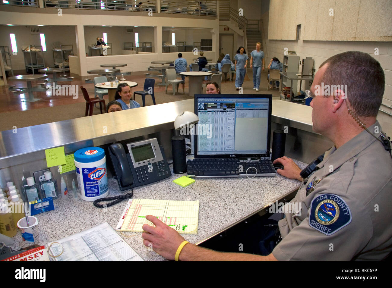Security officer monitoring the female inmate dormitory of a county jail. - Stock Image