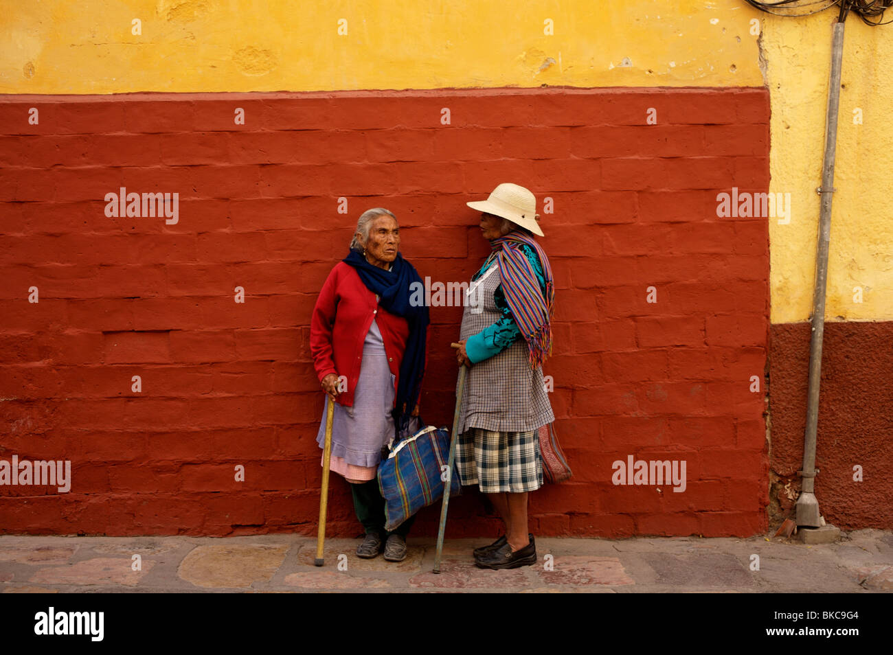 Two women chat along the sidewalk in San Miguel de Allende, Mexico - Stock Image