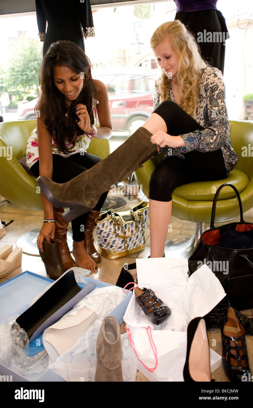 2 teenage girls trying on boots - Stock Image