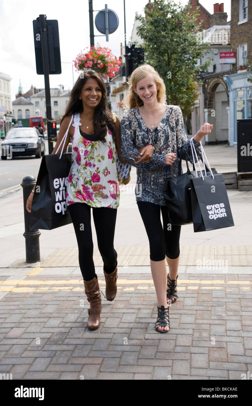 2 Teenage Girls Walking Together Arm In Down A High Street Holding Shopping Bags