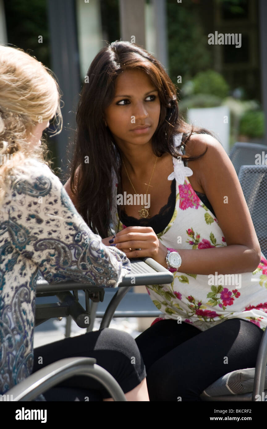 2 teenage girls chatting together with one of them looking shifty - Stock Image