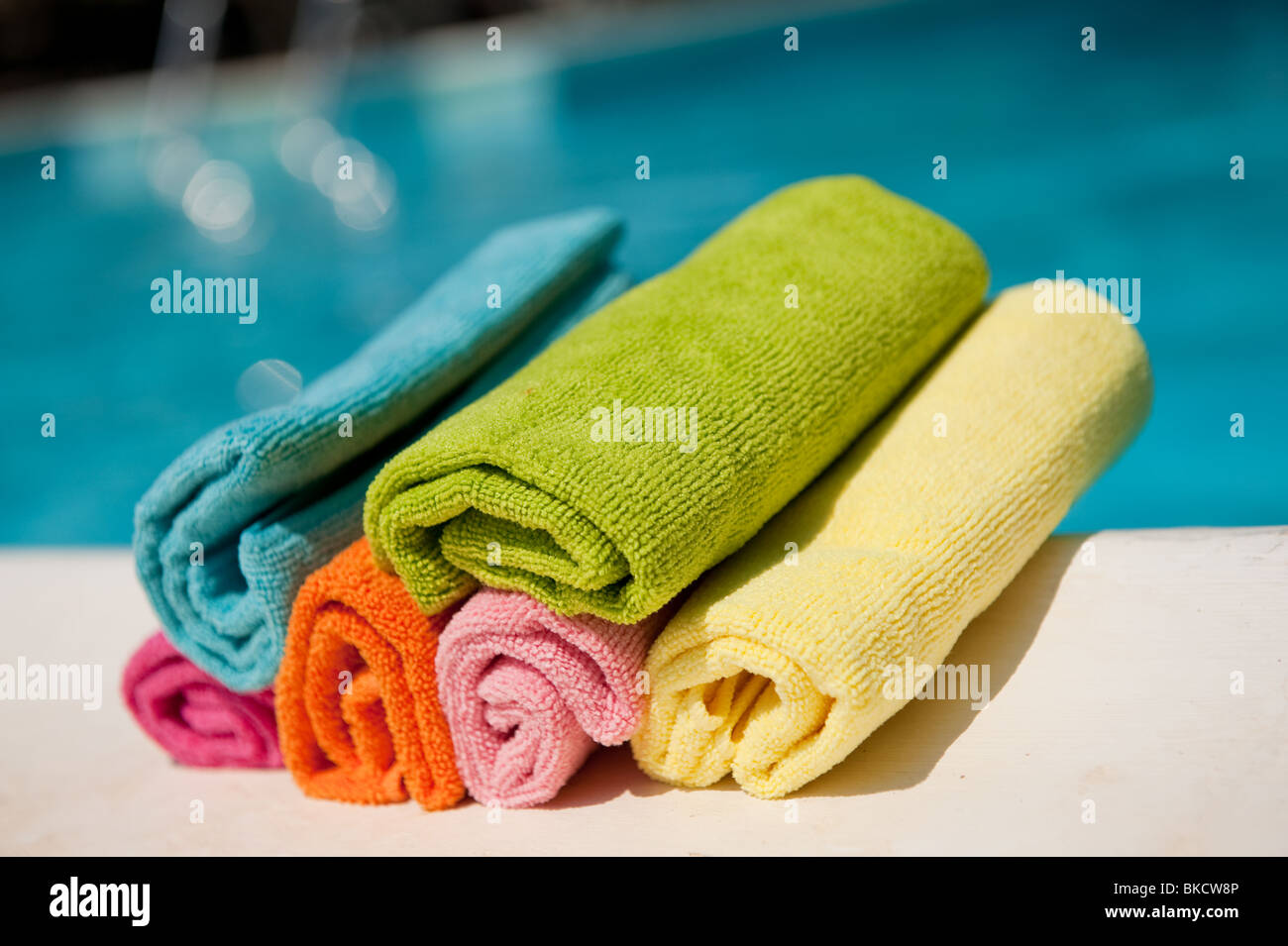 Colorful rolled towels near the swimming pool - Stock Image