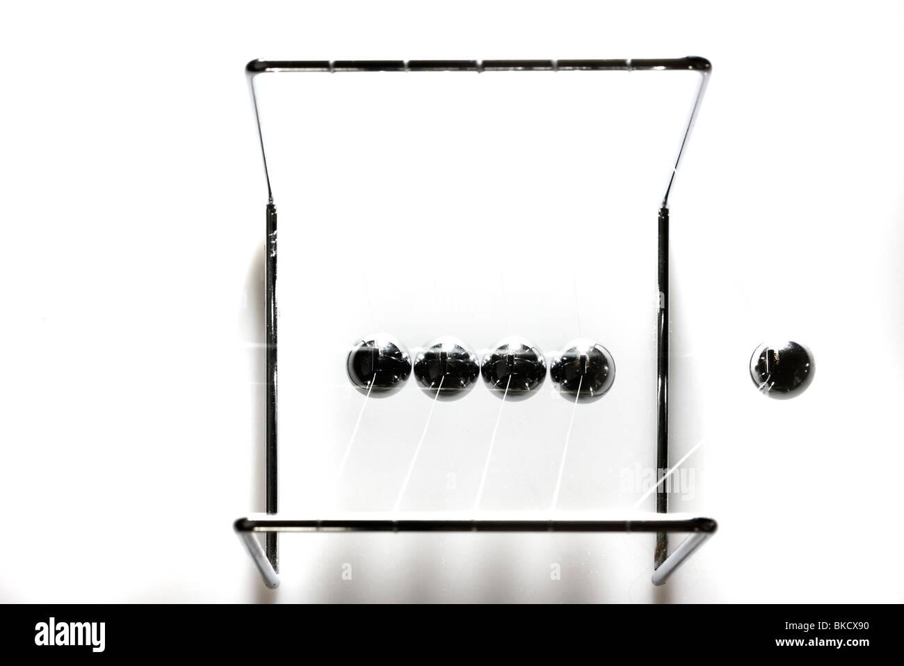Pendulum, chrome balls, toy, gives impulses. Newton pendulum. Stock Photo