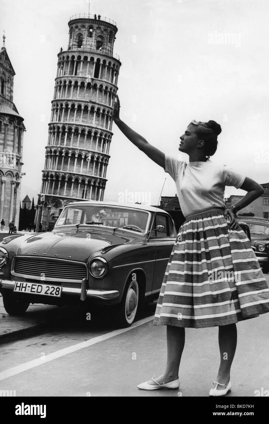 tourism, italy, typical tourist pose, woman sustaining the Leaning Tower of Pisa, 1960s, , Additional-Rights-Clearances - Stock Image