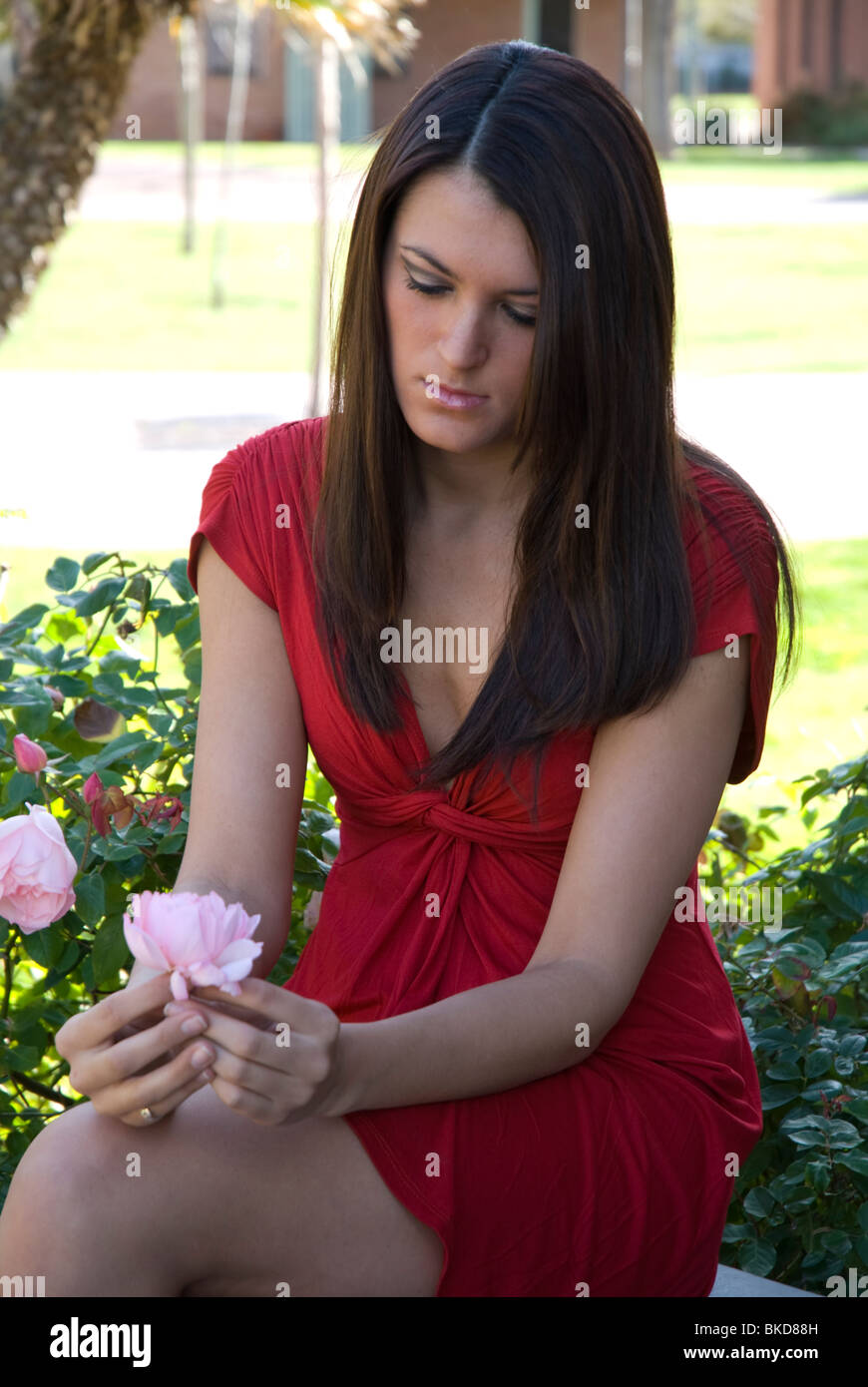 A young adult college age woman looks sadly at a flower. - Stock Image