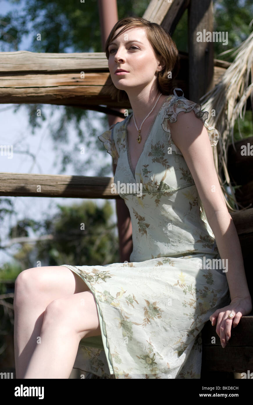 A Beautiful Young Caucasian Woman Sits On Some Old Wooden