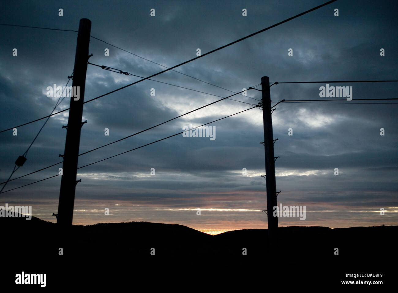 Sunset and silhouetted power powerlines in Wales. - Stock Image