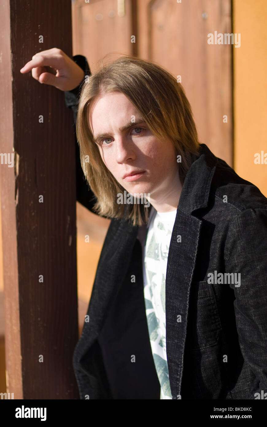 An 18-20 year old man leans on a post looking tough (vertical) - Stock Image