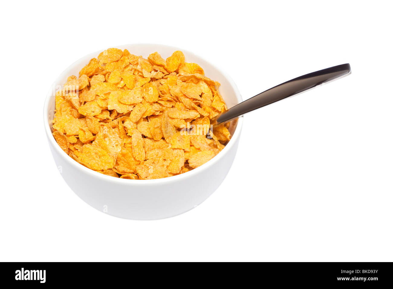 Cornflakes breakfast cereal in a white bowl with spoon - Stock Image