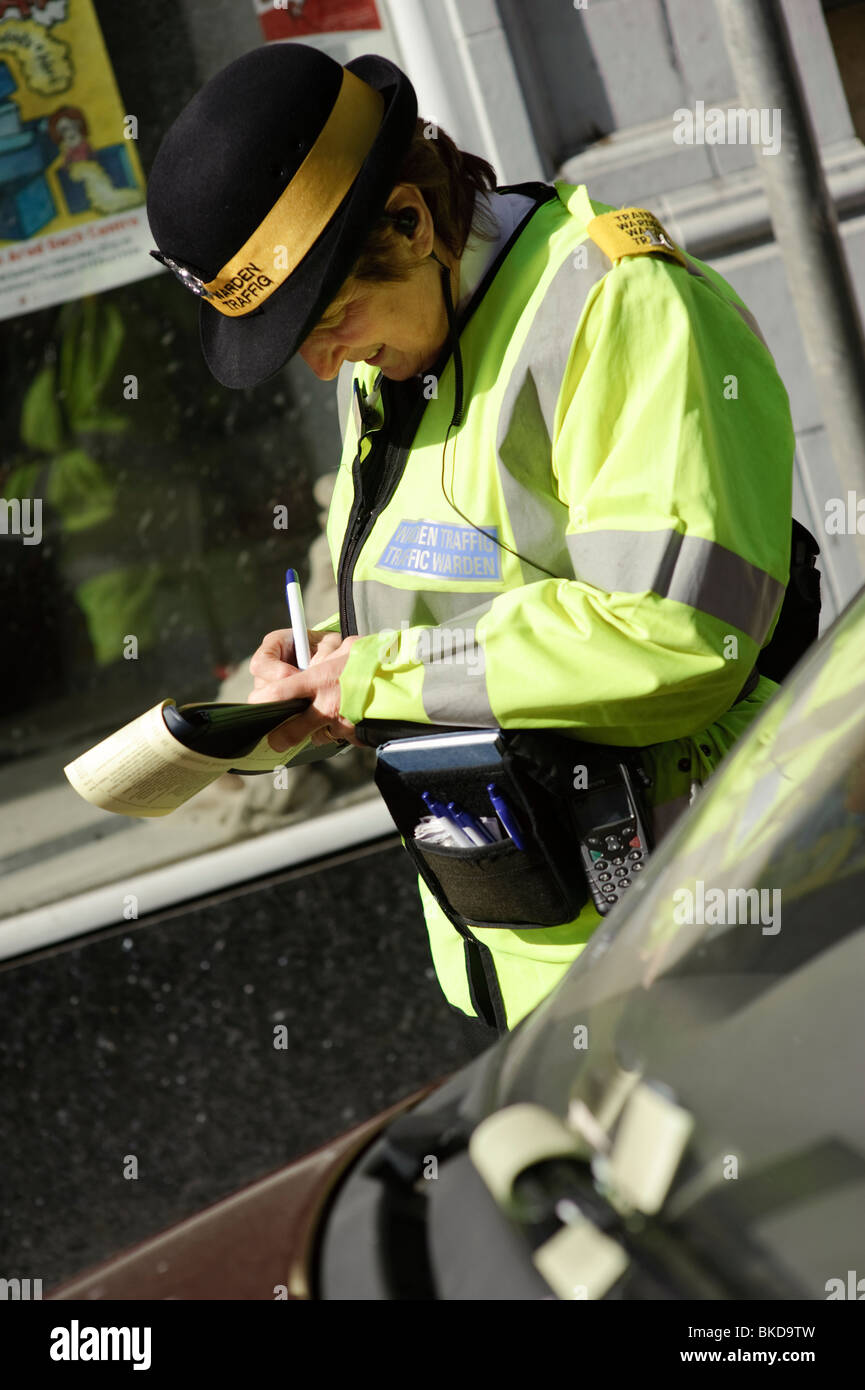 A woman traffic warden issuing a parking ticket for a car that already has two tickets issued already, Aberystwyth - Stock Image