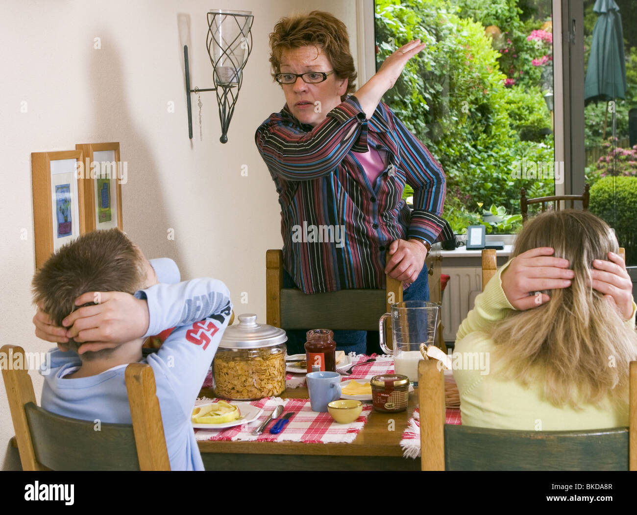 Child abuse at home: Mother smacking her childrenat breakfast table at home and looking very angry. SerieCVS417009 - Stock Image