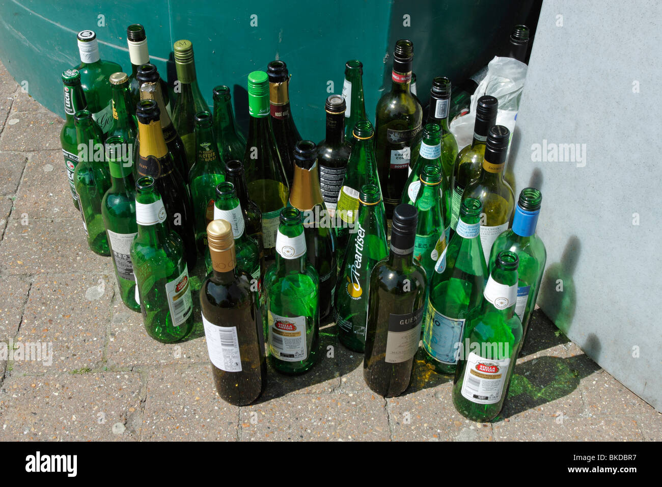 Lots of empty beer and wine bottles beside bottle banks. - Stock Image