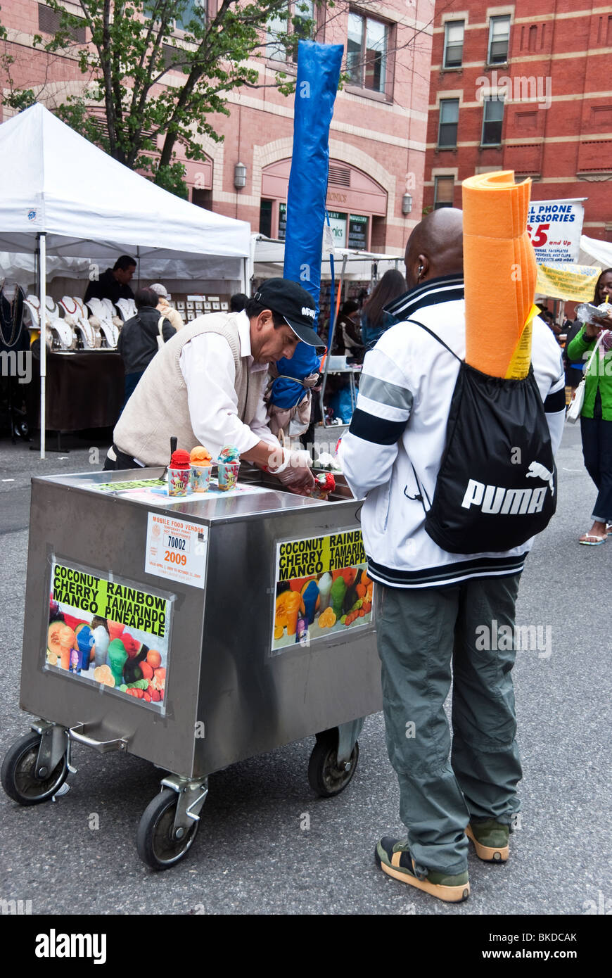 black man buying shaved Italian ice from Ninth Avenue mobile vendor at New York's 9th Ninth Avenue International - Stock Image