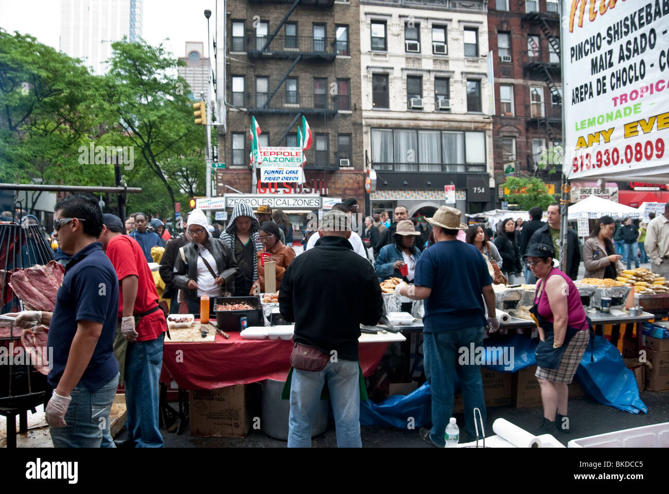 diverse polyglot people crowd around open air stand on Ninth Avenue at New York's 9th Ninth Avenue International - Stock Image