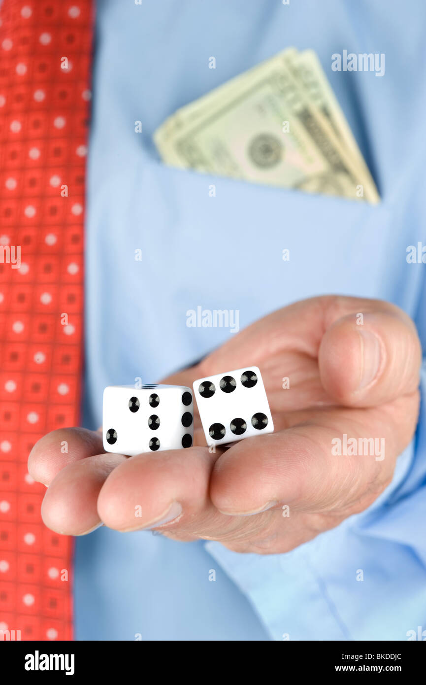 A businessman with a pocket full of cash holds a pair of dice - Stock Image
