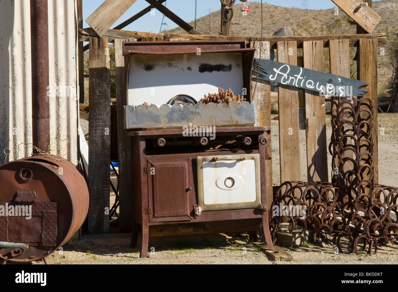 Old stove, horseshoes and other items in front of antique store in Randsburg, California - Stock Image
