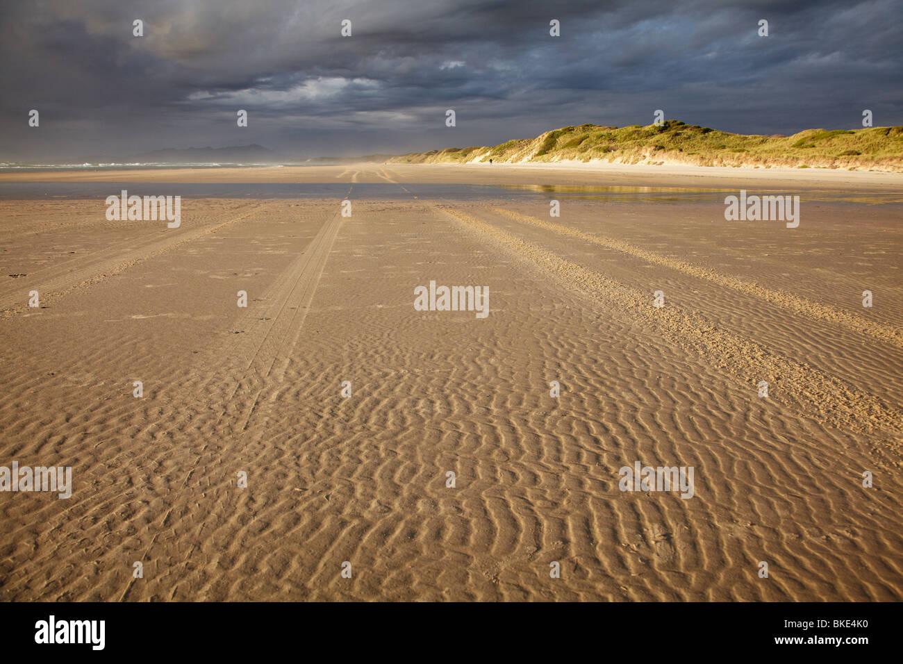 Sand Ripples, Tire Tracks, and Storm Clouds, Ocean Beach, near Strahan, Western Tasmania, Australia - Stock Image