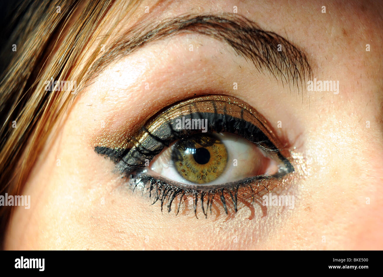 Close Up Of Female Eye Wearing Black And Gold Makeup Stock Photo