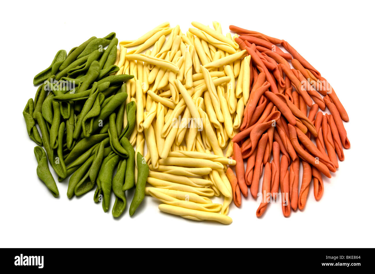 Mixed pasta with the colors of the Italian flag on a white background - Stock Image