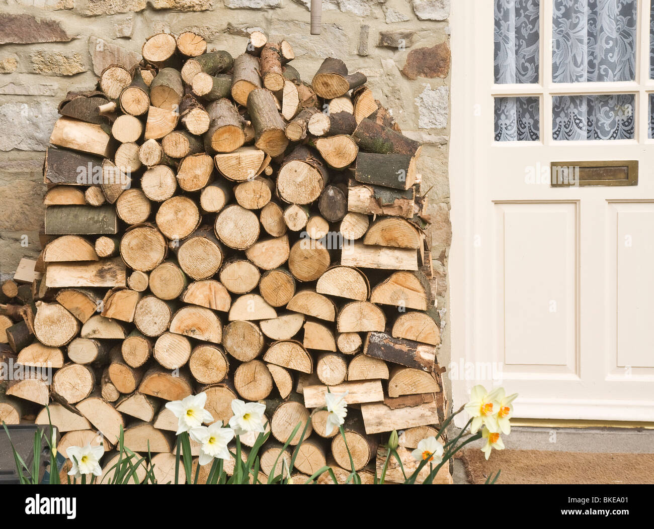 firewood stacked outside a cottage door in the Yorkshire Dales. - Stock Image
