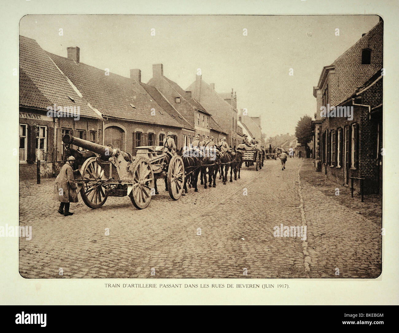 Belgian artillery soldiers transporting cannons by horse through village Beveren in Flanders during First World - Stock Image