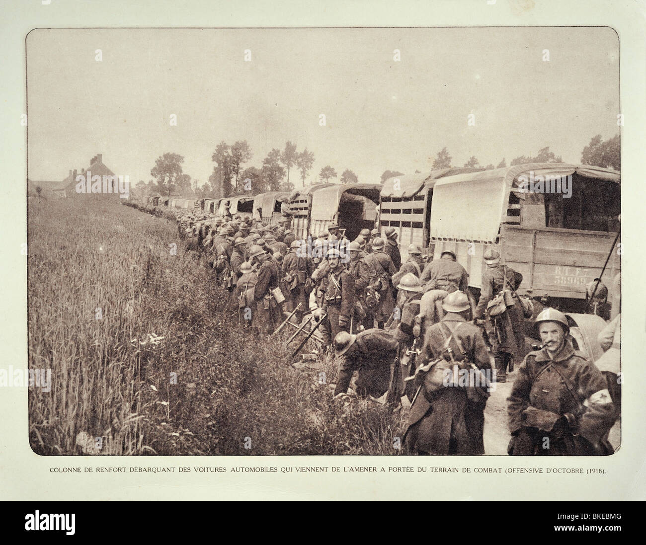 Trucks and WWI soldiers of reinforcement convoy heading for battlefield in West Flanders during First World War - Stock Image