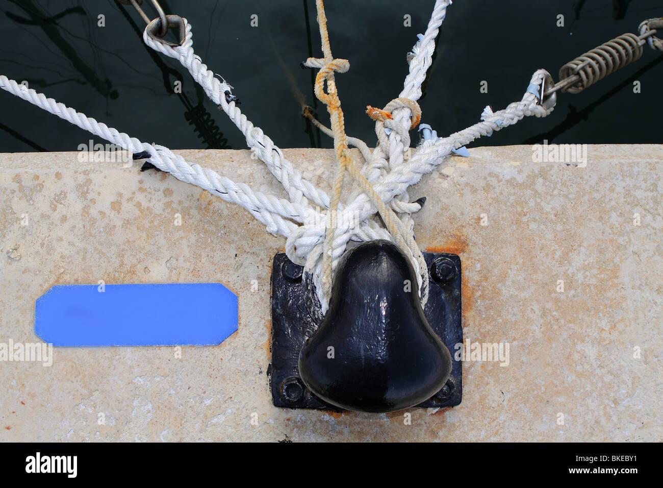 black bollard with many nautical ropes around - Stock Image