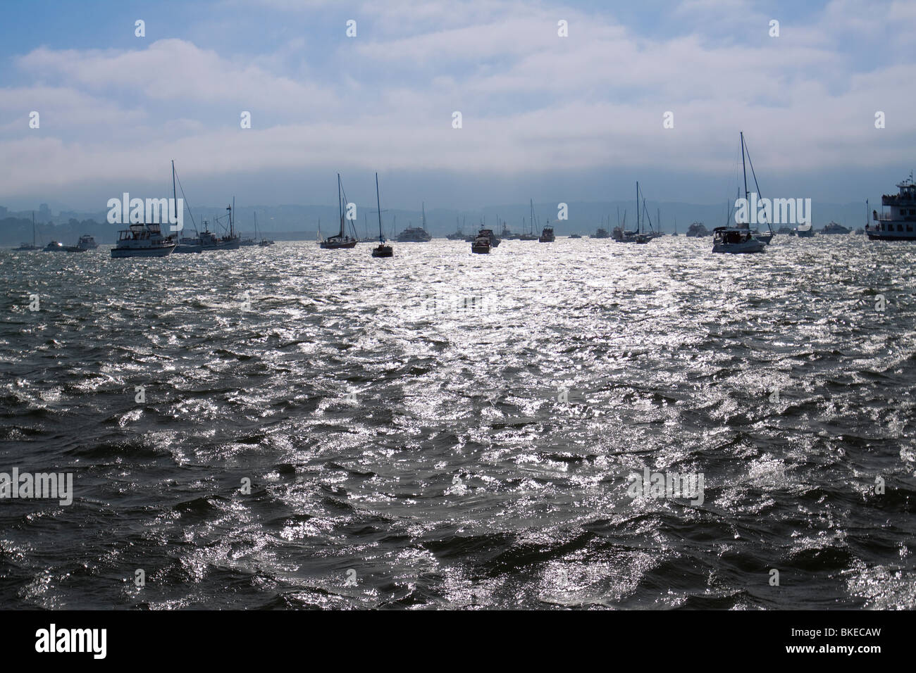 Many boats bobbing in the distance with sun glaring on the water on San Francisco Bay in California - Stock Image