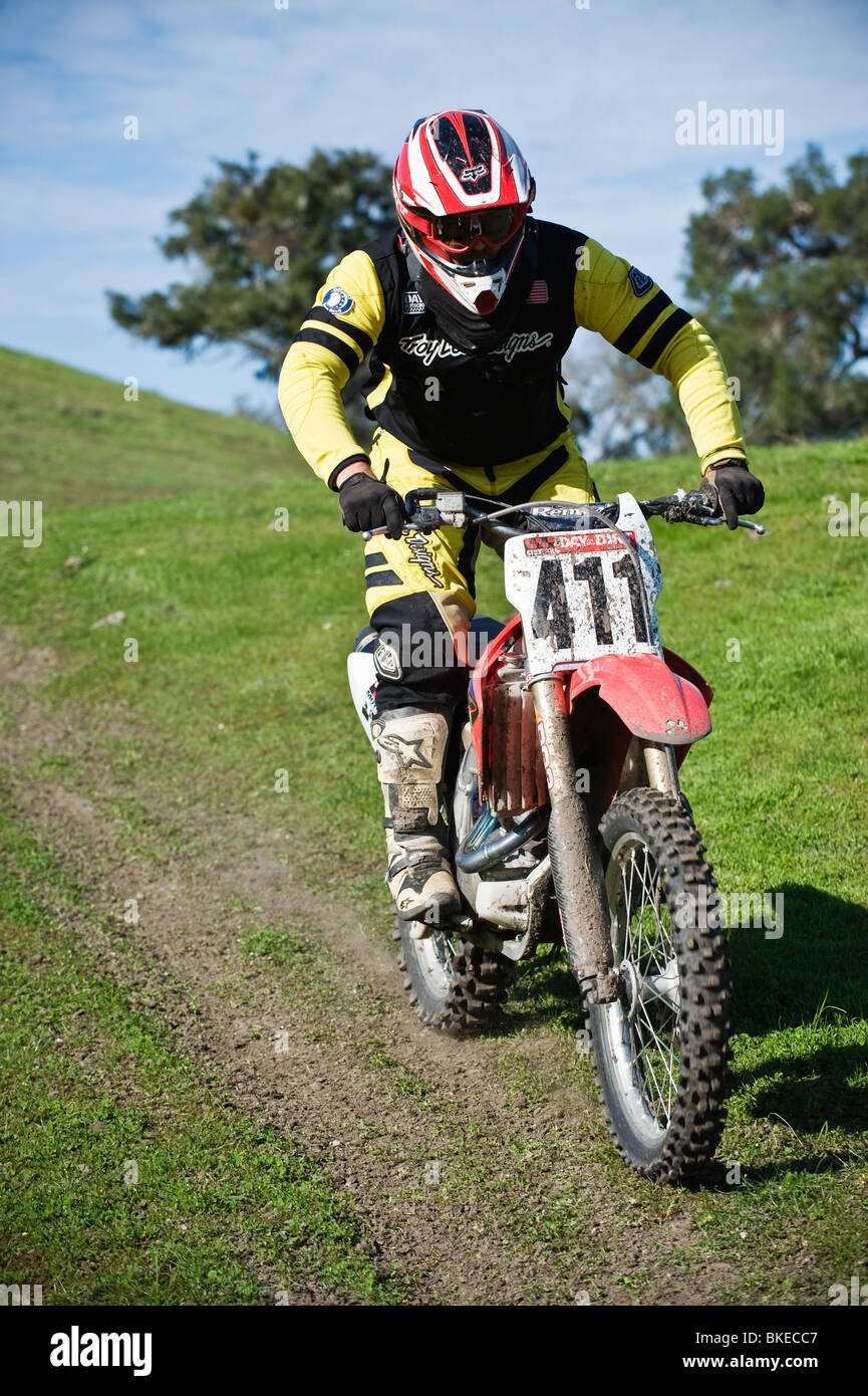Adult male dirtbike rider on dirt trail, California - Stock Image