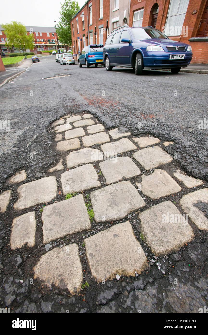 Old cobbled street revealed underneath tarmac on an Oldham Street Lancashire UK - Stock Image
