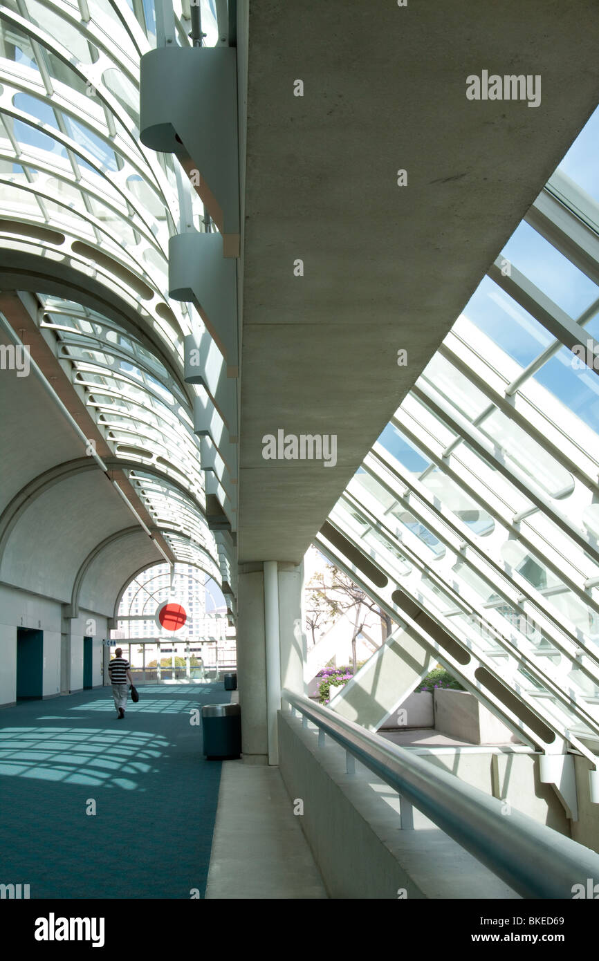 Man walking down hallway with curved glass ceiling in San Diego Convention Center, California - Stock Image