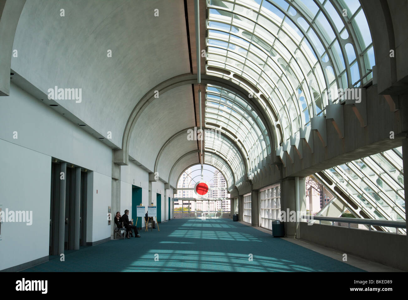 Sparsely populated hallway in San Diego Convention Center with curved glass ceiling - Stock Image