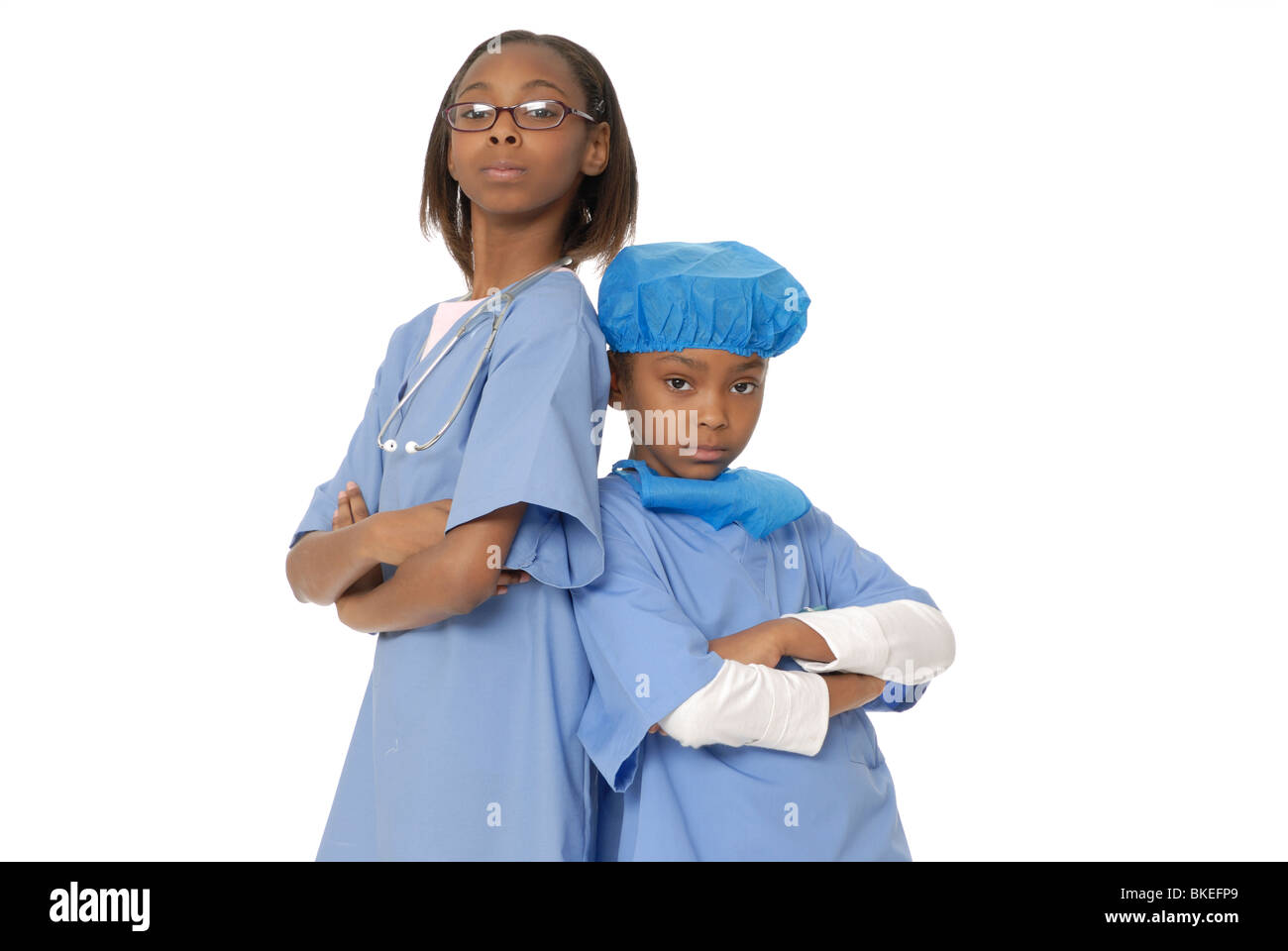 Two girls, ten and six year old sisters, dressed as doctors. - Stock Image