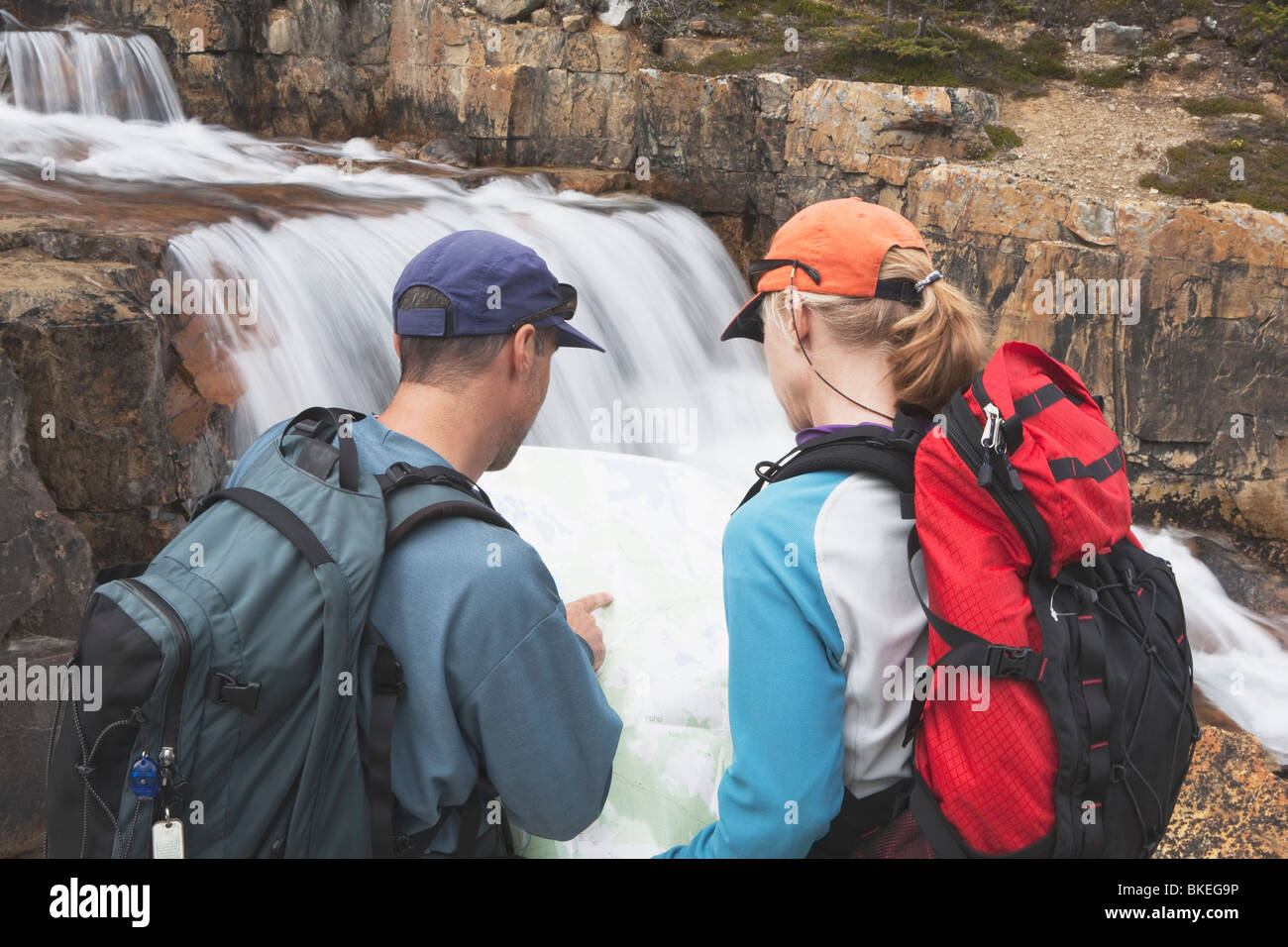 Lake Louise, Alberta, Canada; A Couple Hiking And Looking At A Map Next To The Waterfall At Giant Steps - Stock Image
