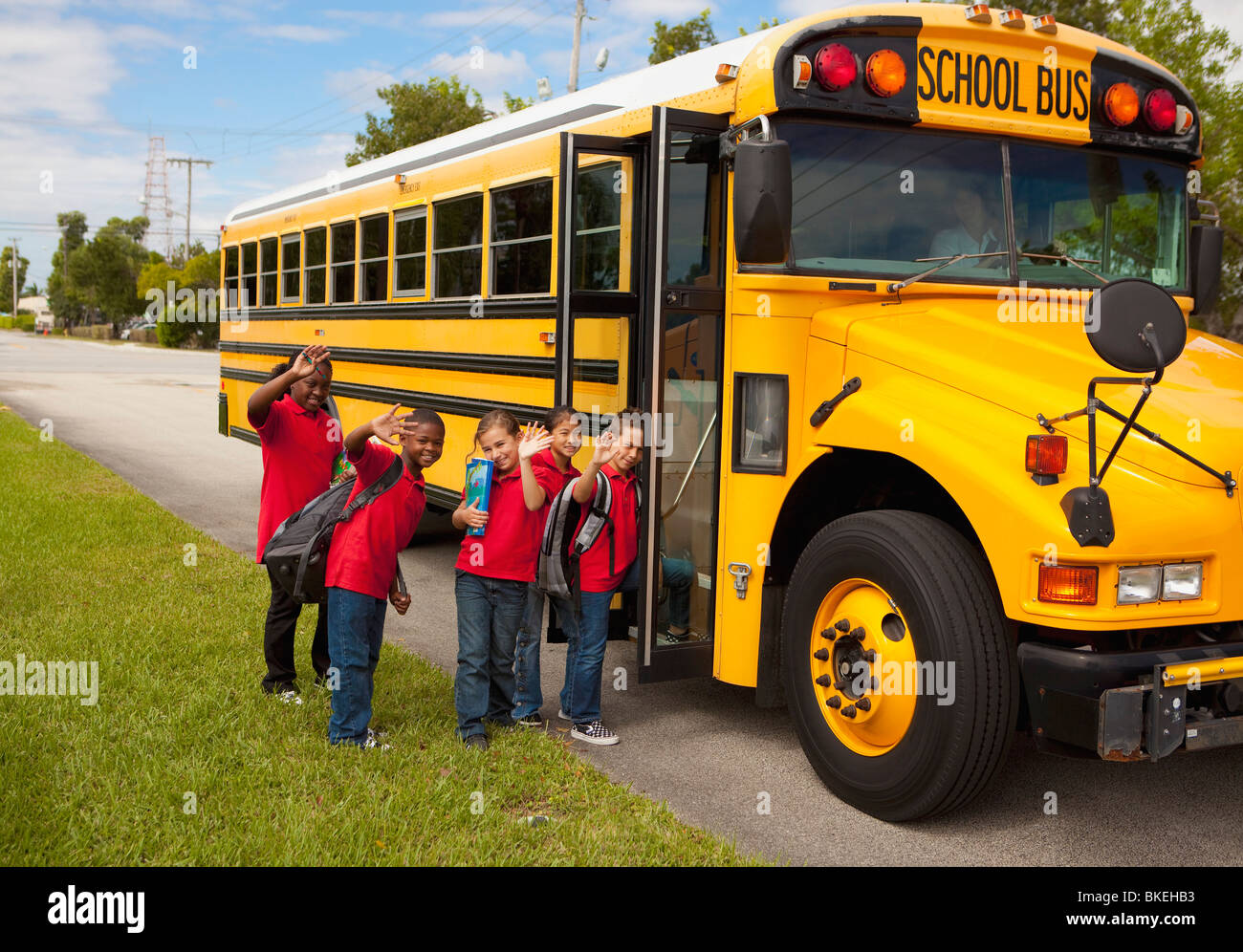 Students Lining Up To Get On The School Bus - Stock Image