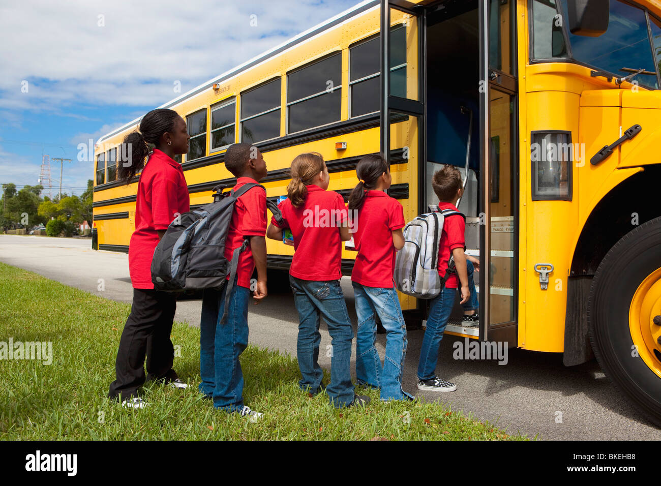 Students Lined Up To Get On The School Bus - Stock Image