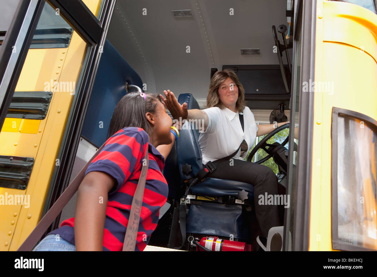 Student And School Bus Driver Slapping Hands In A 'high Five' - Stock Image