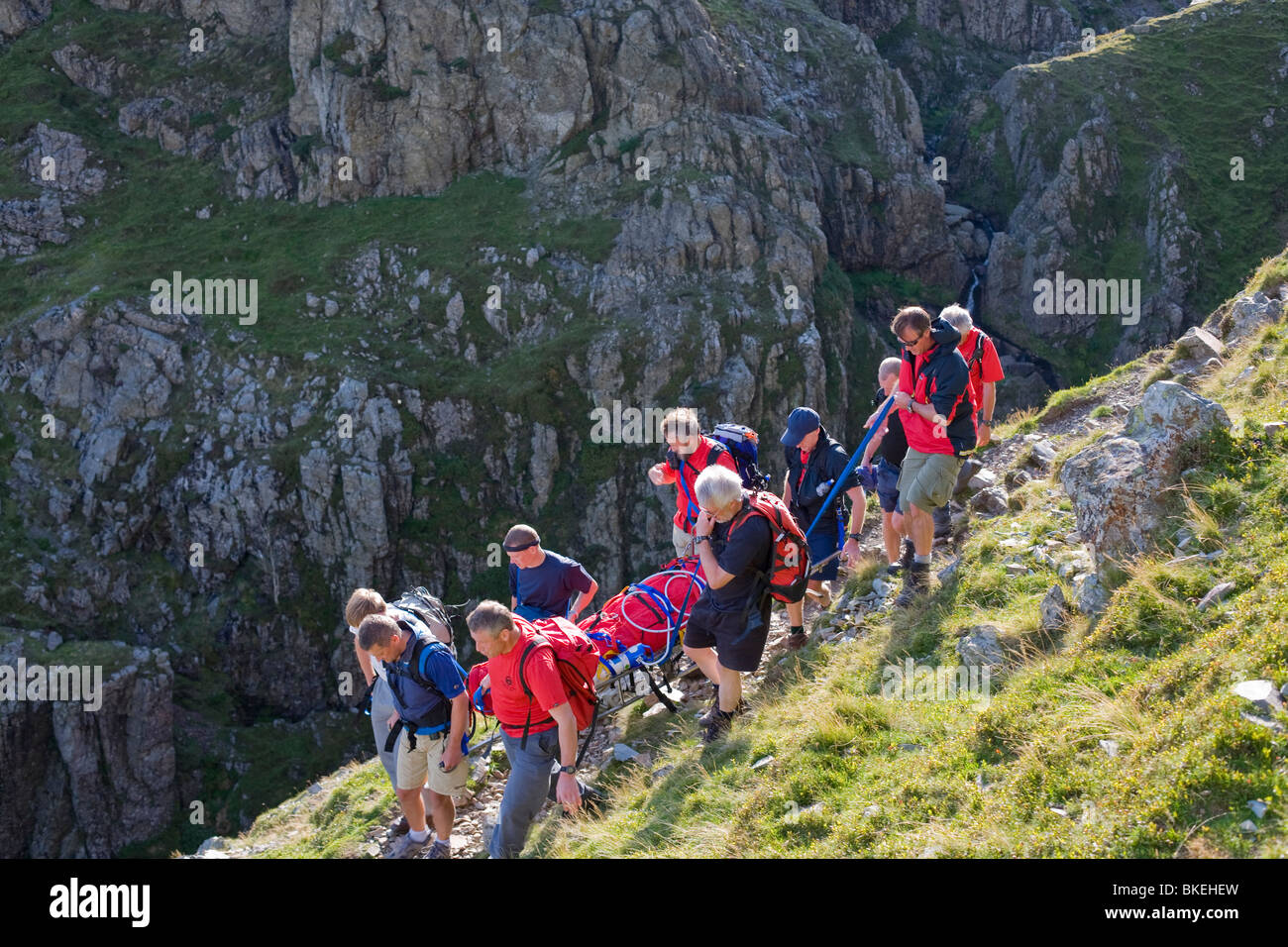 Members of Langdale Ambleside Mountain Rescue Team carrying an injured walker from the fells in Langdale Cumbria - Stock Image