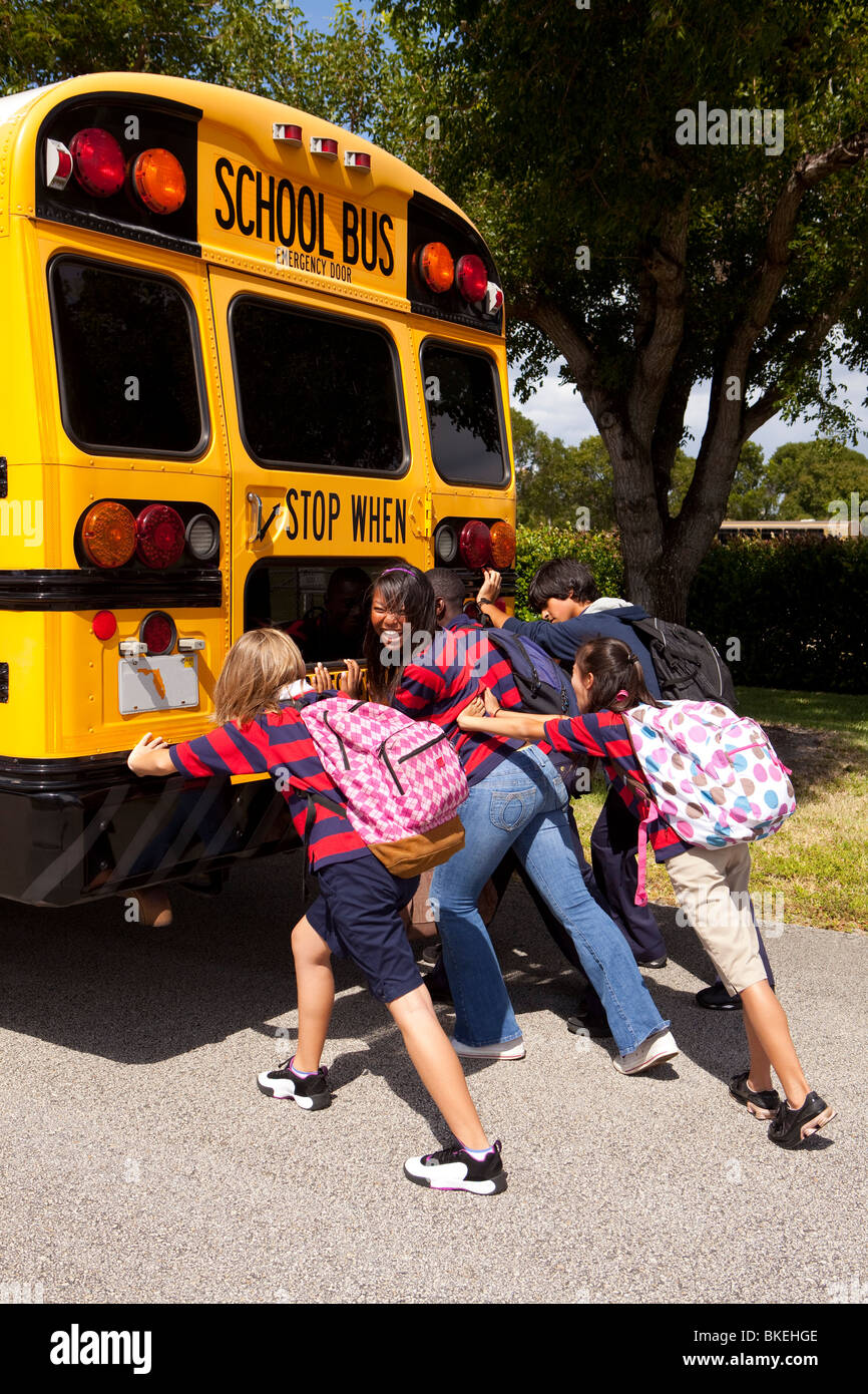 Students Pushing The Back Of The School Bus Stock Photo