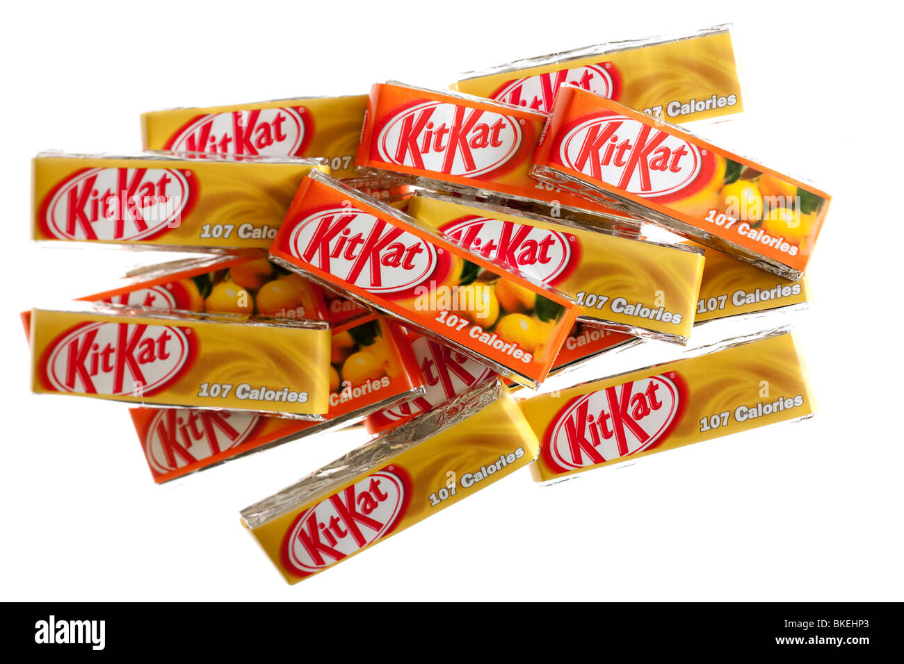 Pile of individual two finger packs of caramel and orange flavoured Nestle KitKat biscuits - Stock Image