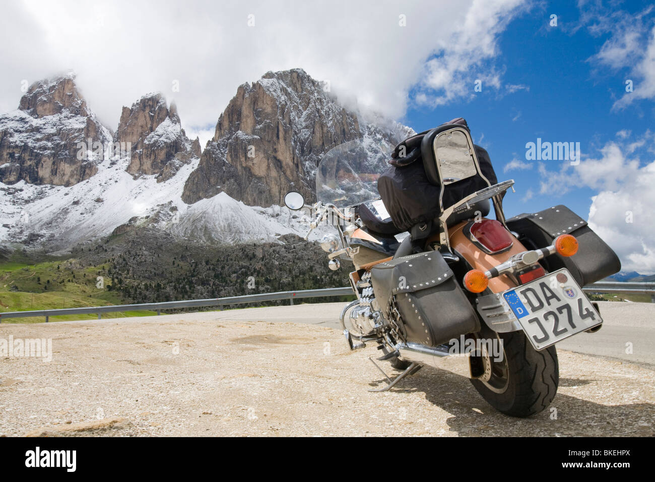 A Motorbike on the summit of the Sella Joch pass in the Italian Dolomites with mountain view behind - Stock Image