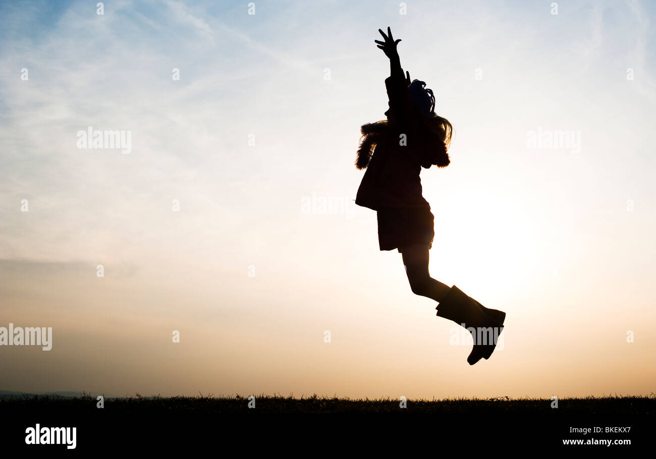 Young Girl energetically having fun jumping around. Silhouette - Stock Image