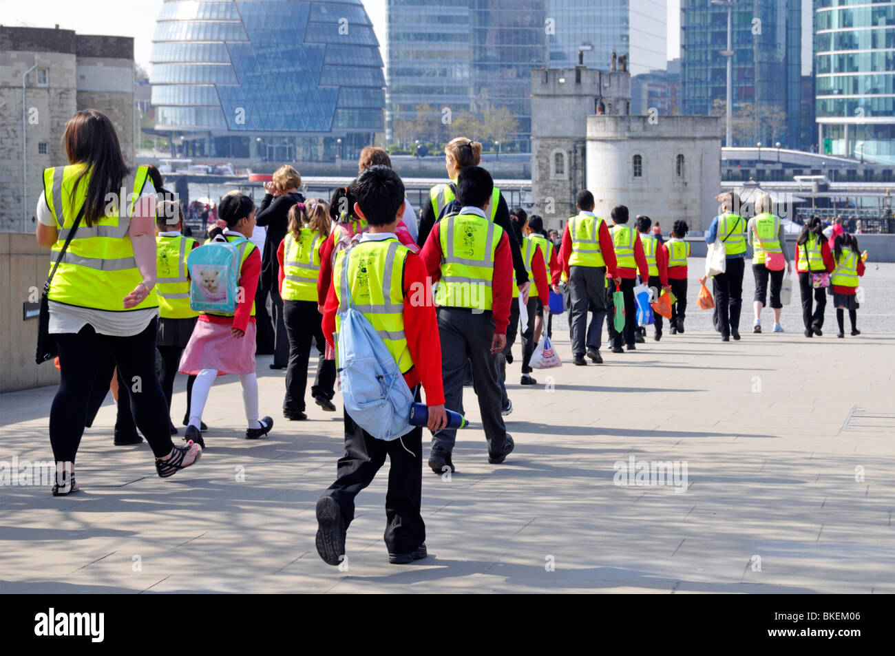 School trip pupils and adults wearing high visibility jackets on visit  to The Tower of London - Stock Image