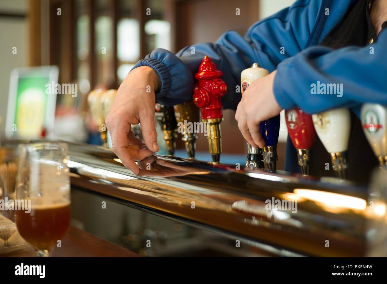 Bartender's hands resting on beer taps. - Stock Image